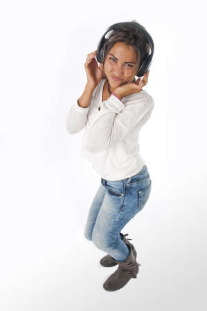 Full length portrait of young woman with casual clothing, on white background,  enjoying music with hands on headphones. photo