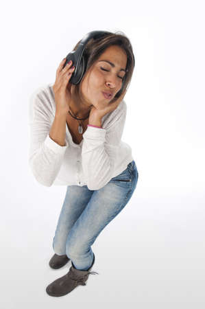 Full length portrait of young woman with casual clothing, on white background, enjoying music dancing with hands on headphones