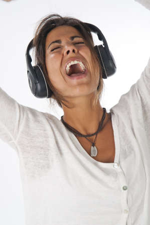 Close-up portrait of happy young female adult with headphones, enjoying listening to music while singing enthusiastically with open mouth