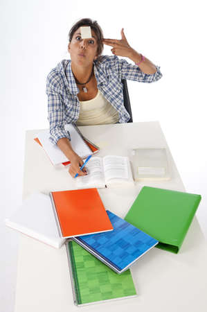 High Angle view of young female tired student in front of table with books and notebooks