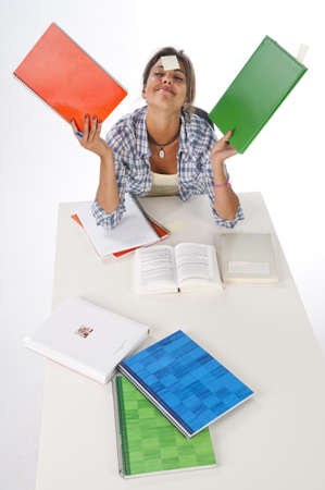 High Angle view of funny happy girl studying on table with books and notebooks on her hands