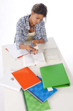 High Angle view of serious and concentrated girl studying on table with books and notebooks