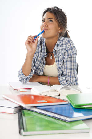 Young female student daydreaming with books and notebooks on table.
