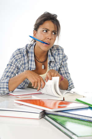 Young female student concentrated studying with books and notebooks on table  Stock Photo - 14938100