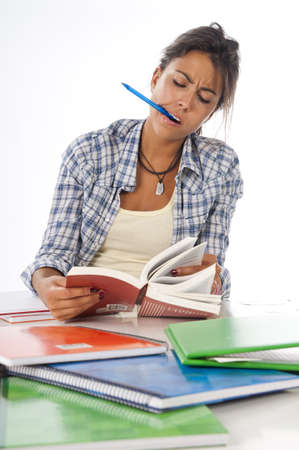 Young female student concentrated studying with books and notebooks on table