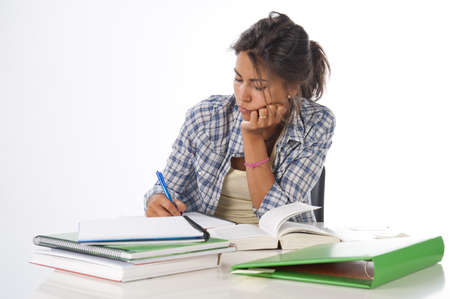 postgraduate: Young female student concentrated studying with books and notebooks on table.