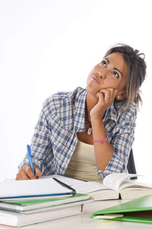 Young female student daydreaming with her future, with books and notebooks on table.