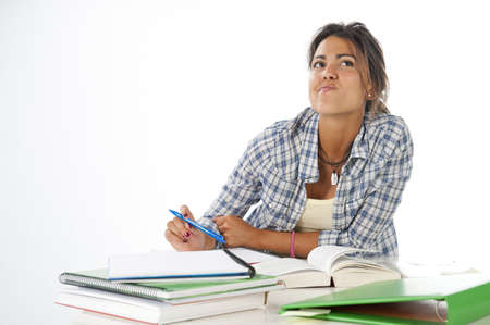 Thoughtful young female student daydreaming with her future, with books and notebooks on table. Stock Photo