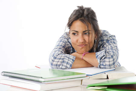postgraduate: Thoughtful young female student daydreaming with her future, with books and notebooks on table. Stock Photo