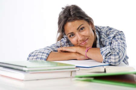 Happy, proud, self-confident young female student with books and notebooks on table. Stock Photo