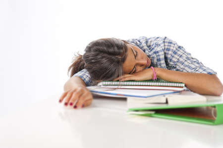 postgraduate: Exhausted young female student with books and notebooks on table.