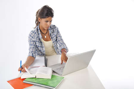Young female student concentrated studying with laptop, books and notebooks on table Stock Photo - 14938084
