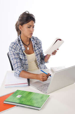Young female student concentrated studying with laptop, books and notebooks on table  Stock Photo - 14938091