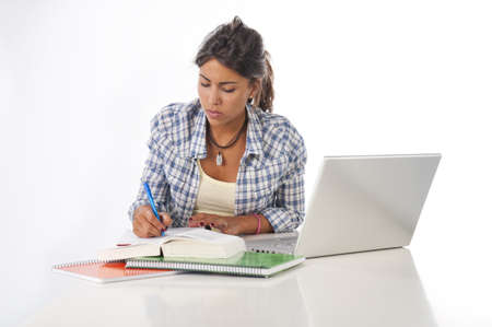 Young female student concentrated studying with laptop, books and notebooks on table. Stock Photo - 14591109