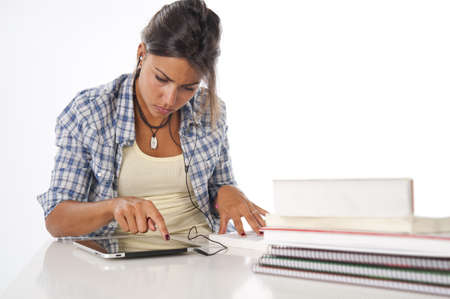 Young female student using tablet PC, with books and notebooks on table. Stock Photo