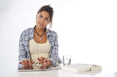 Portrait of young female student working with tablet PC, with book on table looking at camera.