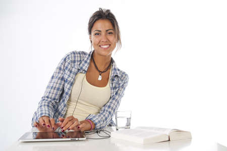 Portrait of self-confident young female student working with tablet PC, with book on table looking at camera.
