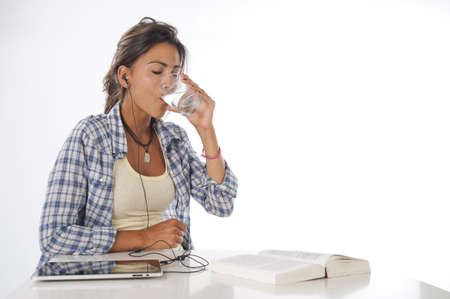 Young female student drinking water with tablet PC, book on table.