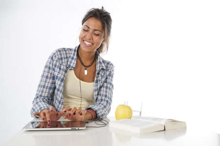 Healthy and happy smiling young female student with book, apple and glass of water, using tablet PC. Stock Photo
