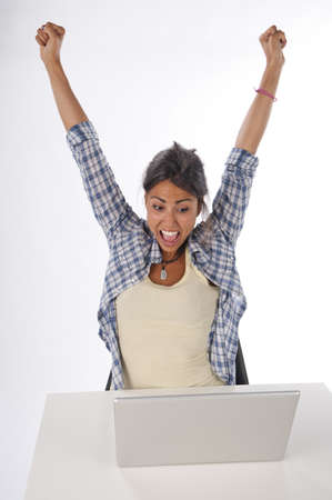 Cheerful girl in front of Laptop with hands up. photo