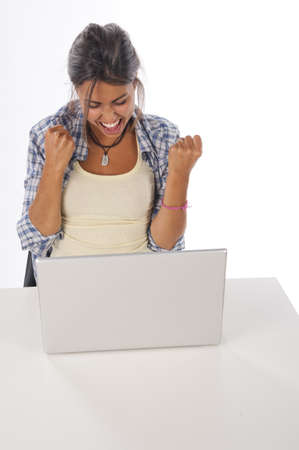 Cheerful girl in front of Laptop with hands up.