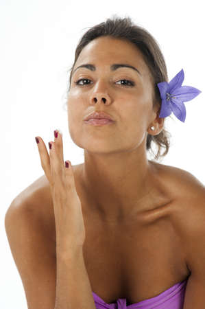 Close-up, beauty portrait of serene young latin woman with flower on hair, with cream on her finger and looking at camera.