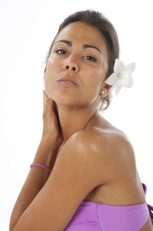 Close-up, beauty portrait of serene young latin woman with flower on hair, gently holding her neck, looking at camera.
