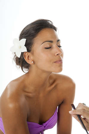 Beautiful latin girl with brown skin applying make up on her face with brush photo