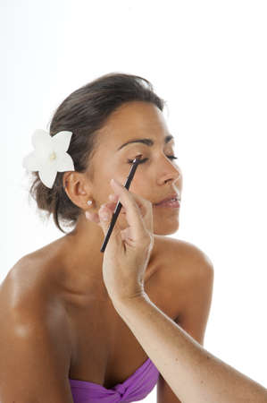 Beautiful latin girl with brown skin applying make up on her face with eyeshadow bruch.