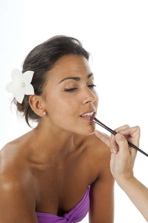 Beautiful latin girl with brown skin applying make up on her face with brush for lips. photo
