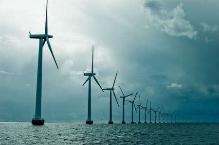 turbine: Windmills in a row on cloudy weather, wide shot, denmark