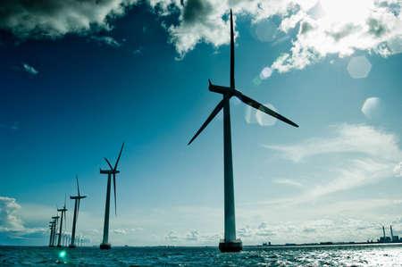 against the sun: Windmills in a row against sun, oresund, denmark, baltic sea Stock Photo
