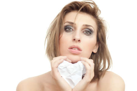 portrait of young beautiful crying woman with paper heart and leaking makeup on white, isolated, copyspace