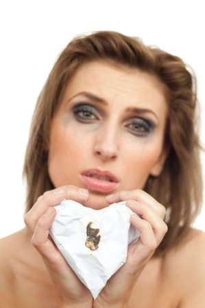 portrait of young beautiful crying woman with paper heart and leaking makeup on white, isolated, copyspace, out of focus