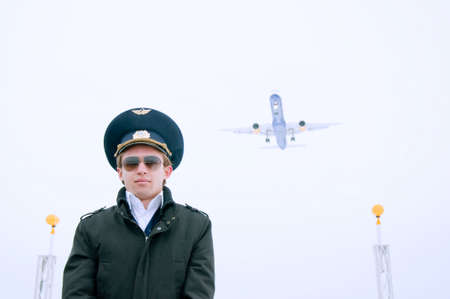 young pilot with glasses and black coat on the landing line with plane, low narrow angle Stock Photo