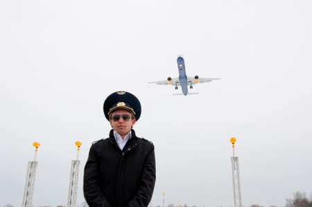 young pilot with glasses and black coat on the landing line with plane, low angle photo