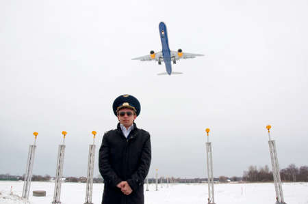 young pilot with glasses and black coat on the landing line with plane, low wide angle