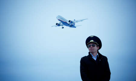 young pilot in glasses with plane on background, low angle, blue tint