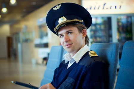 young pilot sitting in the airport on blue chair looking in the camera