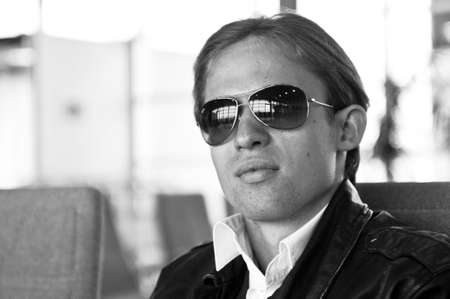 portrait of young man in glasses sitting on blue chairs in the departures in the airport, black and white