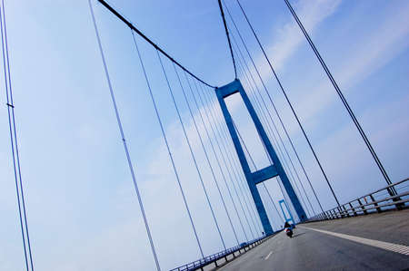 Suspension bridge in Denmark with motorcycle driving on it, scandinavia, diagonal