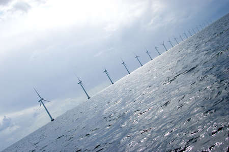 Diagonal shot of windmill turbines in a row in the sea, cloudy weather Stock Photo