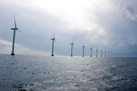 Windmills in a row on cloudy weather, oresund, denmark, baltic sea Stock Photo