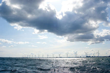 Clouds on blue sky over windmill farm in baltic sea, scandinavia