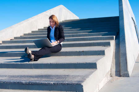 business woman sitting on the stairs with laptop on sunny day, wide
