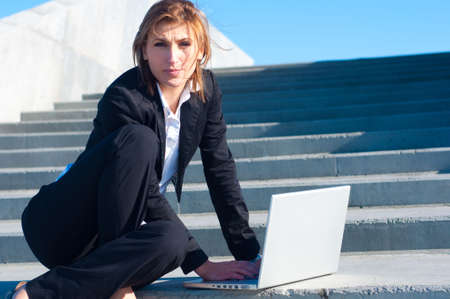 business woman working on stairs with laptop on sunny day Stock Photo