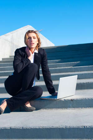 woman stairs: business woman working on stairs with laptop on sunny day, vertical
