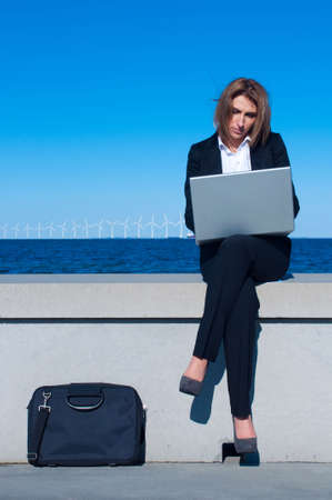 business woman working with laptop on the beach on sunny day