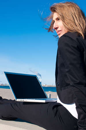 business woman working with laptop on the beach on sunny day, closeup