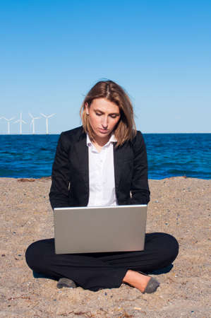 business woman sitting on the sand with laptop on the beach on sunny day, Vertical photo
